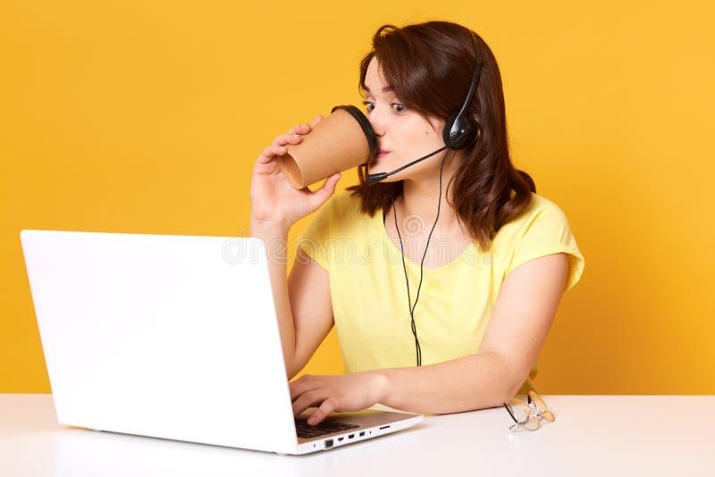演播室被射击年轻深色头发的夫人,工作在电话中心,给咨询客户通过视频通话,有耳机的妇女和 免版税库存照片