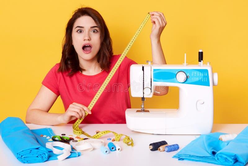 演播室被射击恐慌的年轻深色的裁缝在犯错误以后,当缝合新的成套装备,穿红色偶然T恤杉的夫人,时 免版税库存图片