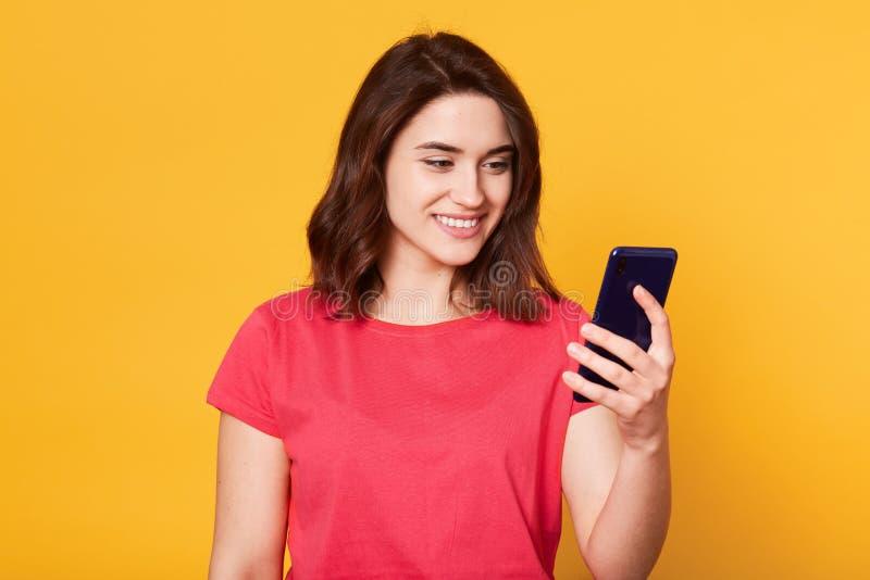演播室被射击有在黄色背景隔绝的黑发的年轻悦目欧洲妇女,在手中拿着智能手机, 免版税库存照片