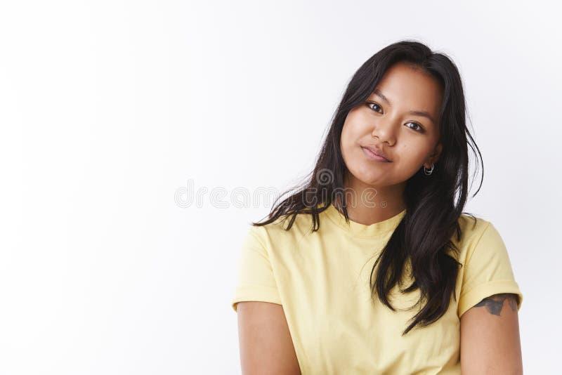 演播室被射击梦想的柔和的年轻可爱的亚洲人女性在黄色T恤杉tiltintg头招标和注视在照相机 库存照片