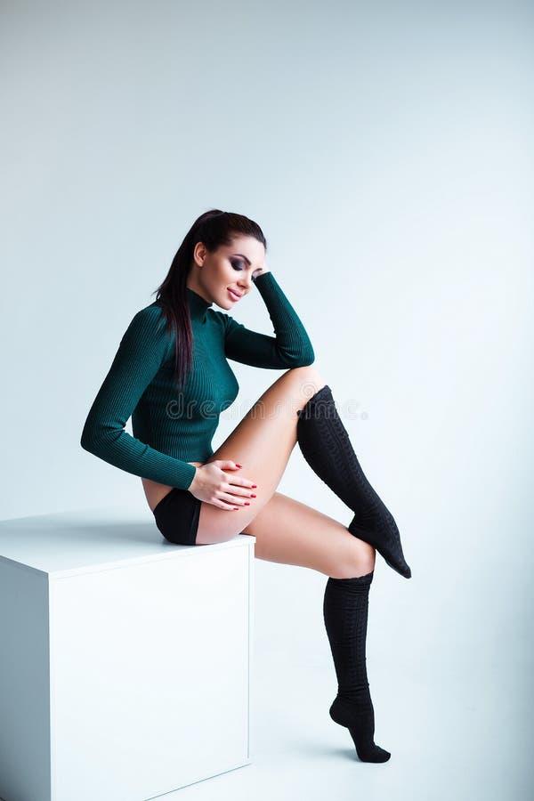 演播室被射击诱惑性感的长腿的年轻女性模型佩带的短裤和膝盖袜子 库存照片