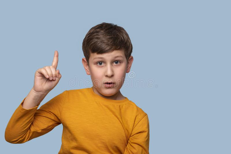 演播室证明某事的射击了男孩通过举他的食指反对与拷贝空间的蓝色背景 图库摄影