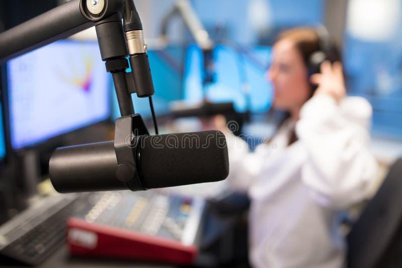 演播室话筒在有女性主人的电台在背景中 免版税库存图片