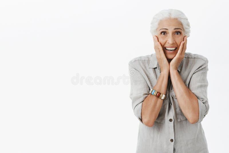 演播室起反应在惊奇的被射击资深妇女 被接触的和高兴逗人喜爱的老妇人画象有白发的 免版税图库摄影