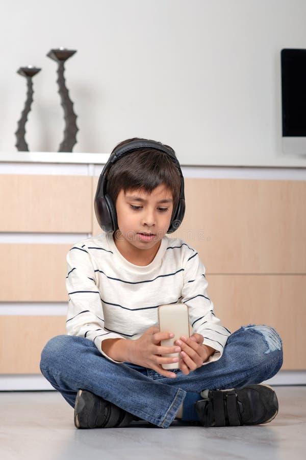 演播室选址在地板上的被射击一个年轻男孩在一间屋子里有耳机的和有电话的 免版税库存图片