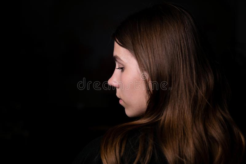 演播室黑背景黑暗的黑色衣服画象女孩晚上招待会外形边深色的头发看边缘框架 r 免版税图库摄影