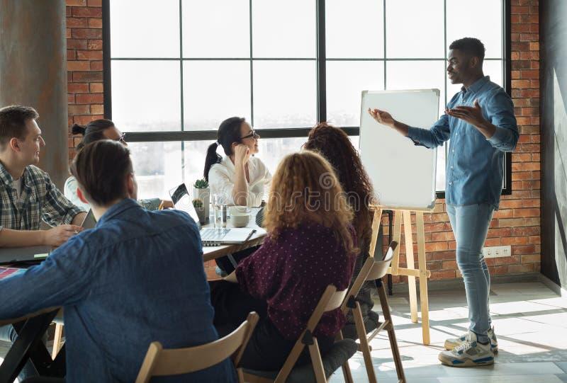 演讲他的雇员的非裔美国人的领导在办公室 免版税图库摄影
