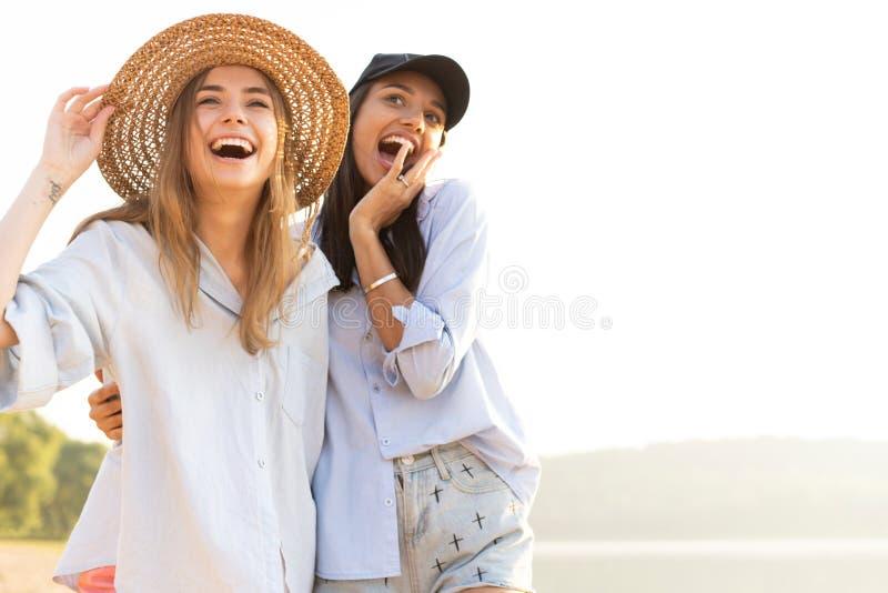 漫步在海滩的两美丽的年轻女人 走在海滩和笑在一个夏日的女性朋友 免版税库存图片