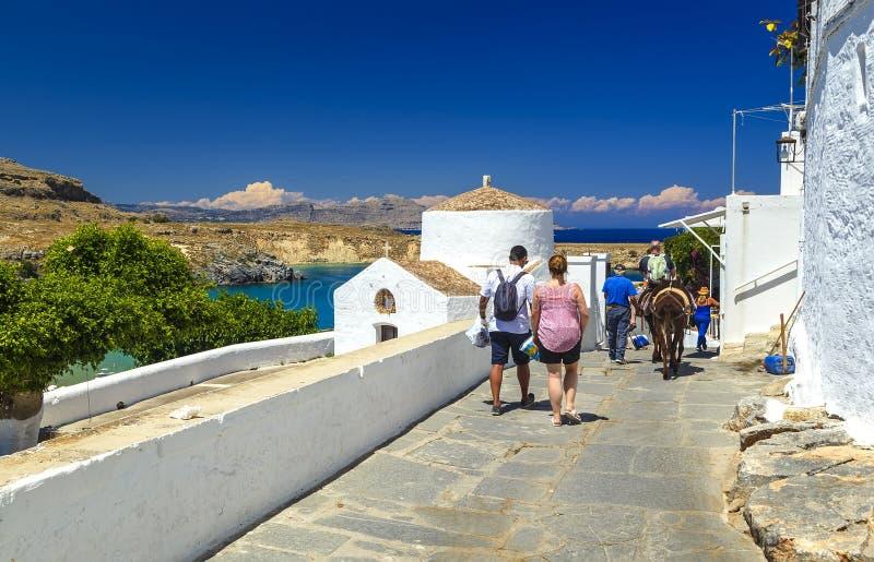 漫步通过街道的一个小组游人 海skyview风景照片海湾和东正教在罗得岛海岛上的Lindos 免版税库存照片
