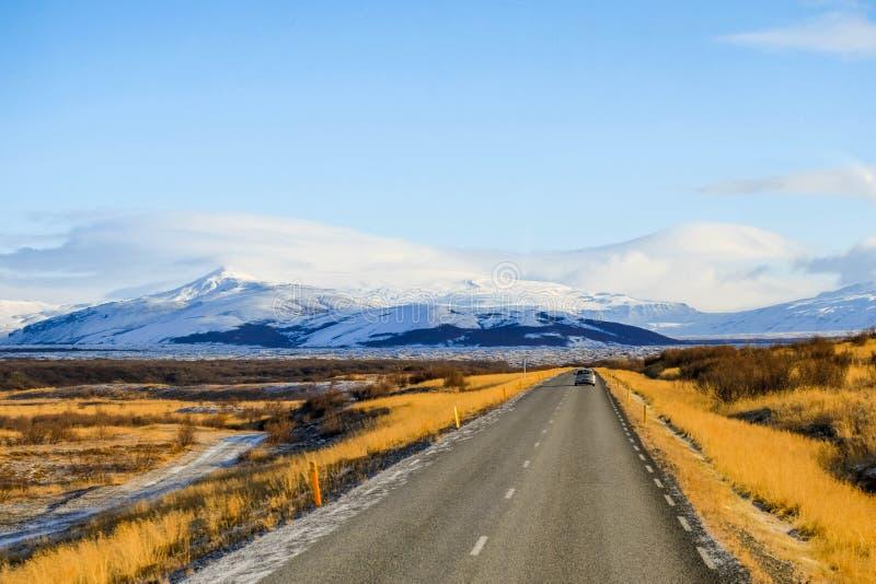 漫长的路在冰岛有雪mounrtain背景和小汽车驱动在路.