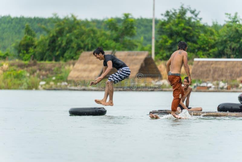 潜水入水的小组十几岁的男孩在河 库存照片
