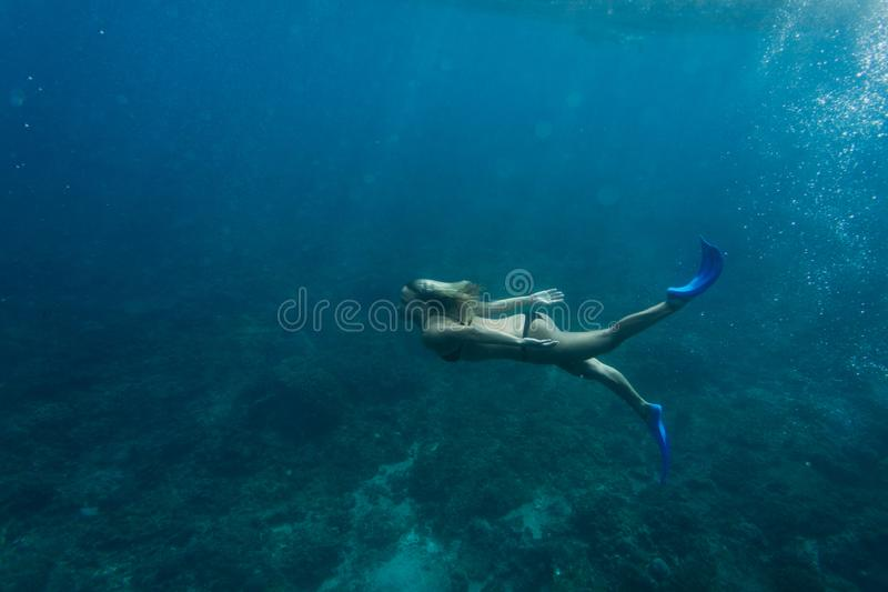 潜水在单独海洋的妇女和鸭脚板侧视图比基尼泳装的 免版税图库摄影