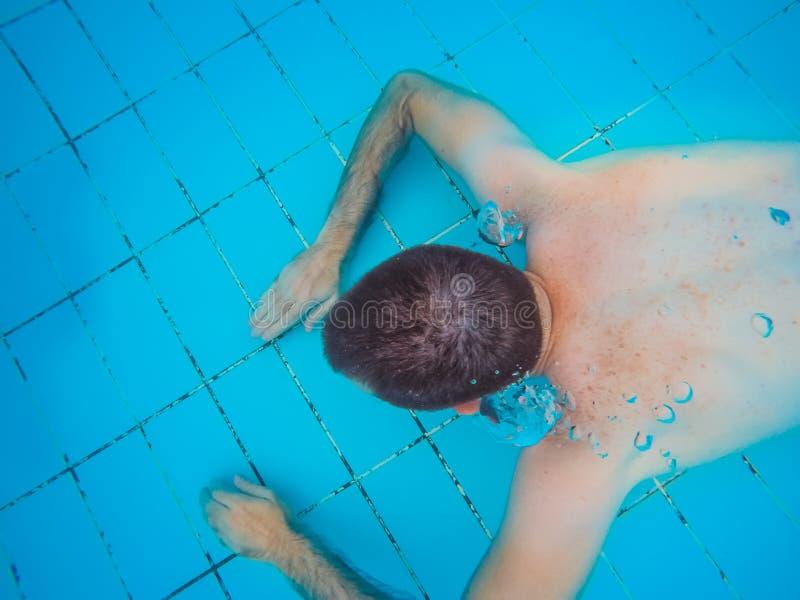 潜水在水面下在游泳的一个年轻英俊的人的顶视图 库存照片
