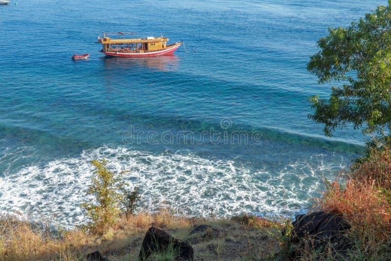 潜水的徒步旅行队小船在海湾停泊 有珊瑚礁的潜水的站点在巴厘岛 在海岸线的海泡沫 免版税图库摄影