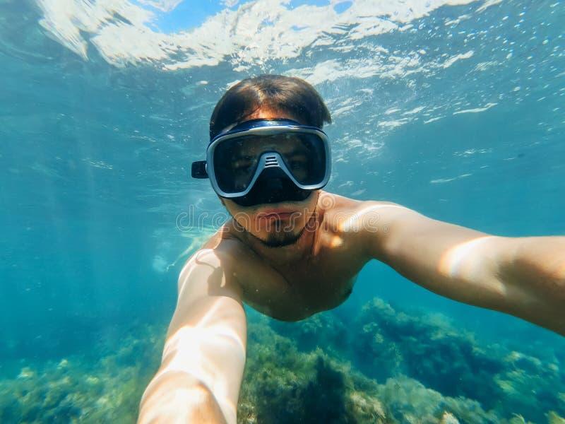 潜水者人游泳的水下的看法在绿松石海在与采取selfie的潜航的面具的表面下 免版税库存照片
