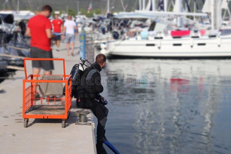 潜水者水肺在小游艇船坞潜水在有航行游艇的码头附近 检查损伤在船水线下在远航以后 库存照片