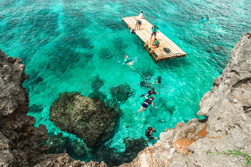 潜航在关于水晶小海湾海岛的岩石海岸的绿松石海的小组中国游客在博拉凯附近 库存图片