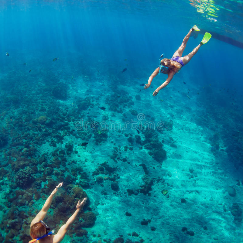 潜航在水面下在珊瑚礁的愉快的夫妇 库存图片
