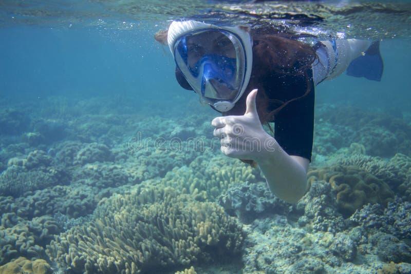 潜航的妇女展示赞许 在热带海珊瑚礁的废气管  正面潜航的面具的少女 免版税库存图片