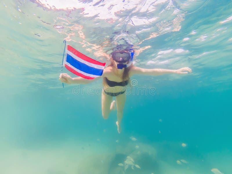 潜航的面具下潜水中的愉快的妇女与与泰国旗子的热带鱼在珊瑚礁海水池 ?? 免版税库存照片