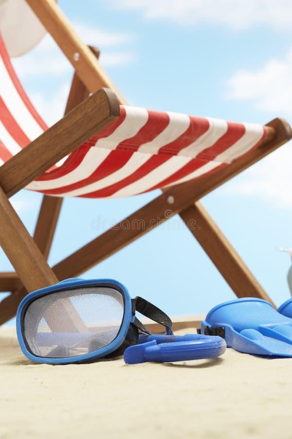 潜航的面具和鸭脚板在deckchair下在海滩 免版税图库摄影
