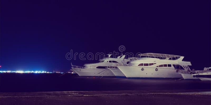 潜水巡航游艇在夜小游艇船坞,减速火箭的样式停泊了 免版税图库摄影