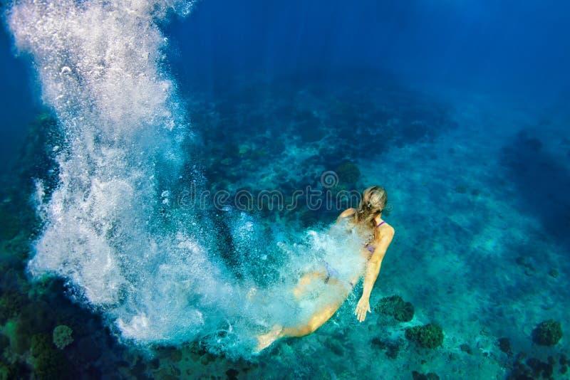 潜水的少妇在水面下 免版税库存图片