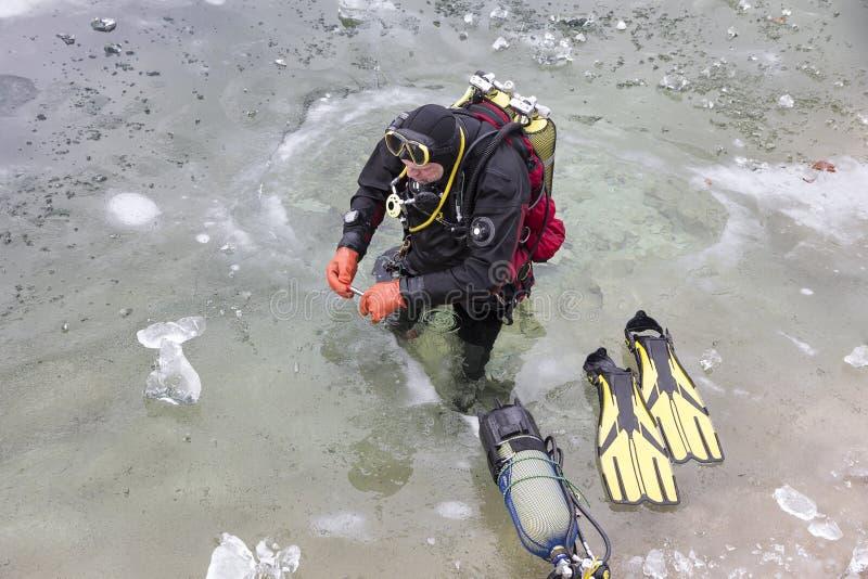 潜水者为冰潜水做准备在l冻结的表面下  免版税图库摄影