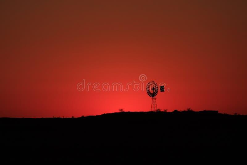 澳洲内地在日出的风车剪影 免版税库存照片