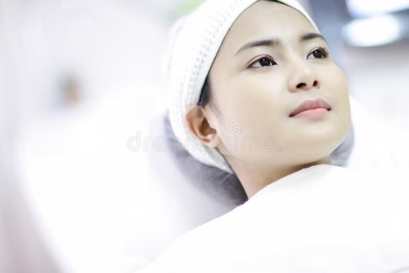 激光机器 得到激光治疗的少妇 应用关心皮肤透明油漆 得到面部秀丽治疗的少妇,取消染色 免版税库存照片