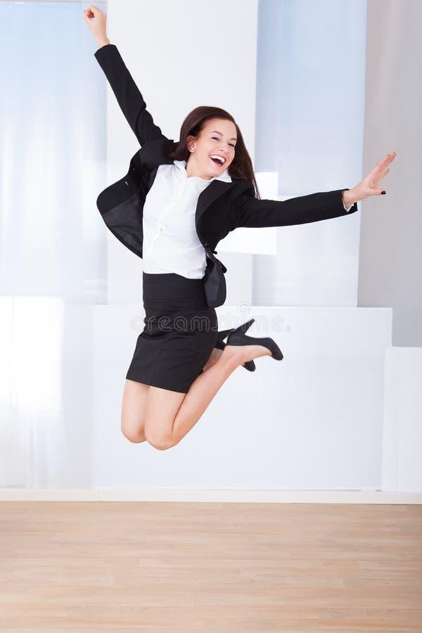 激动女实业家跳跃 免版税库存图片