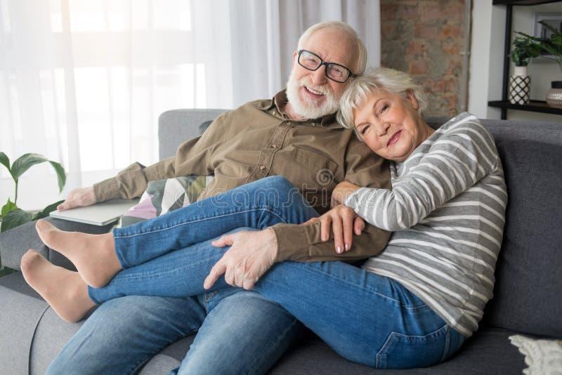 激动拥抱一起享受时间的领抚恤金者在家 免版税库存照片