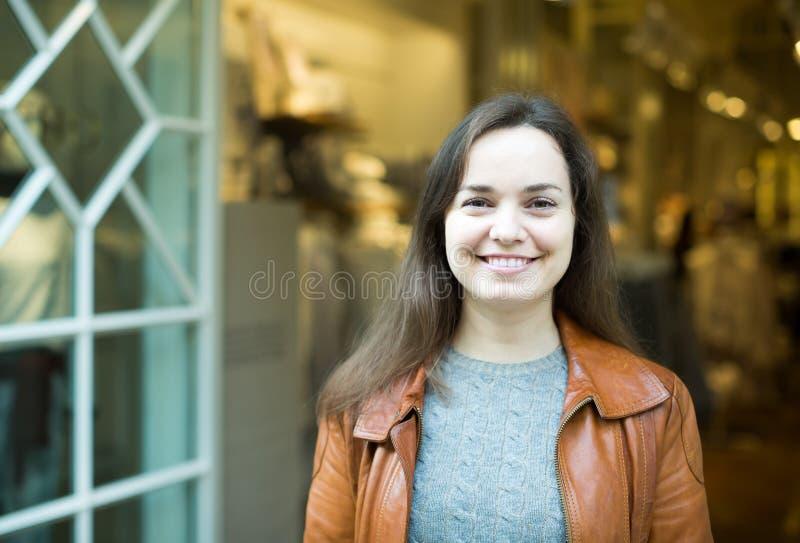 激动深色摆在服装店和微笑 免版税图库摄影