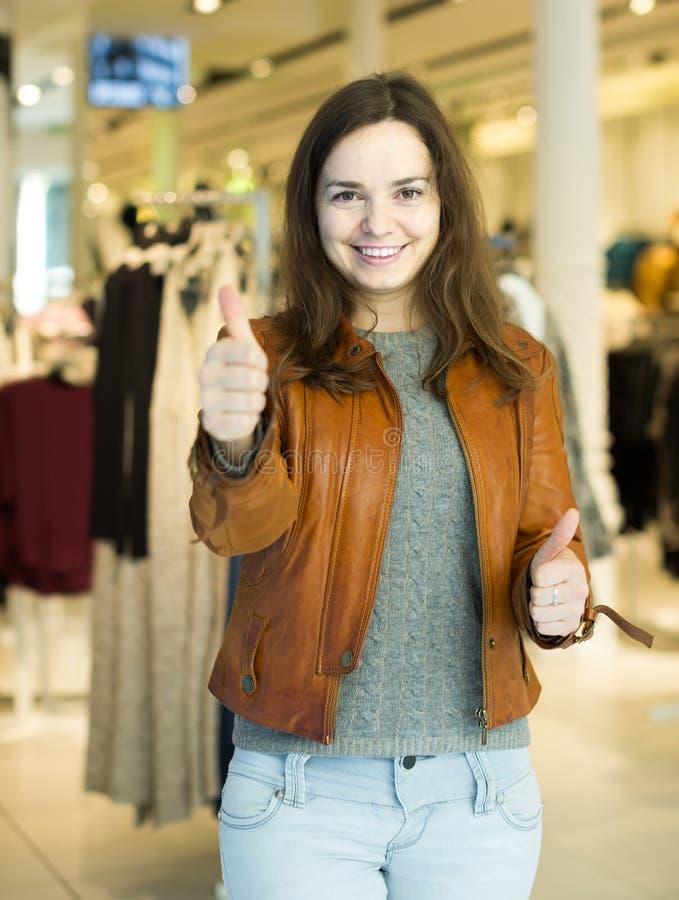 激动深色摆在服装店和微笑 库存图片
