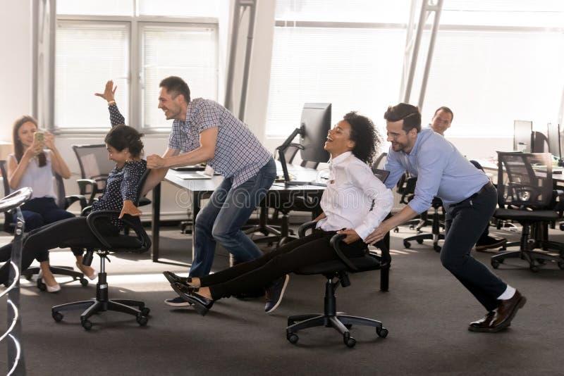 激动的不同的雇员获得乐趣一起在办公室 库存图片