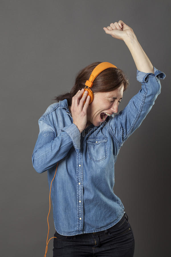 激动的中部变老了享受呼喊的妇女,听到质朴的音乐 图库摄影