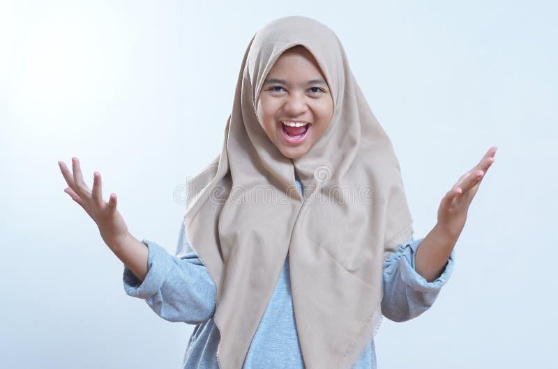 激动的亚洲年轻女人身分的图象被隔绝在灰色背景 免版税库存照片