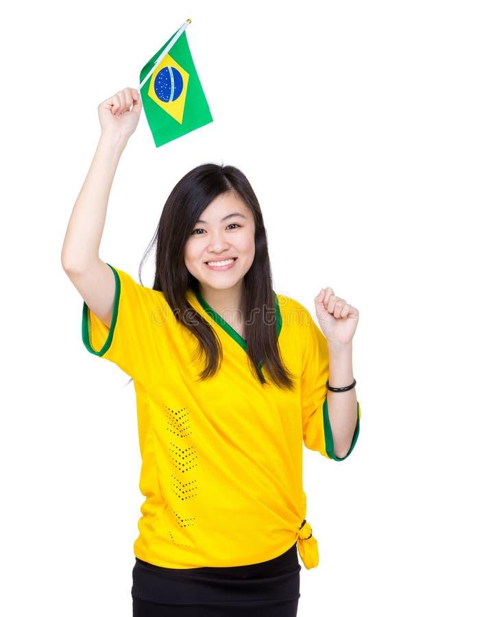激动的亚洲妇女举行巴西旗子 免版税库存图片
