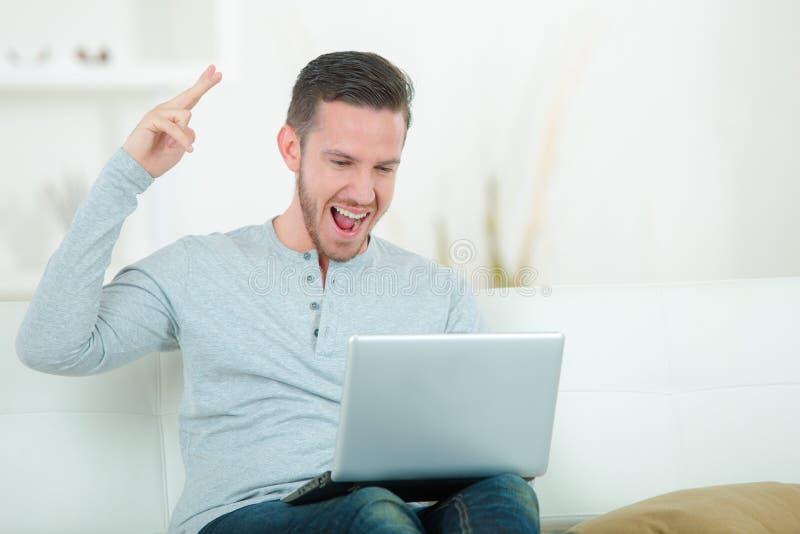 激动的企业家与膝上型计算机一起使用 库存照片