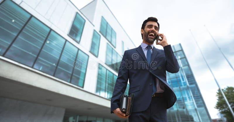 激动的商人谈话在电话反对大厦背景 库存图片