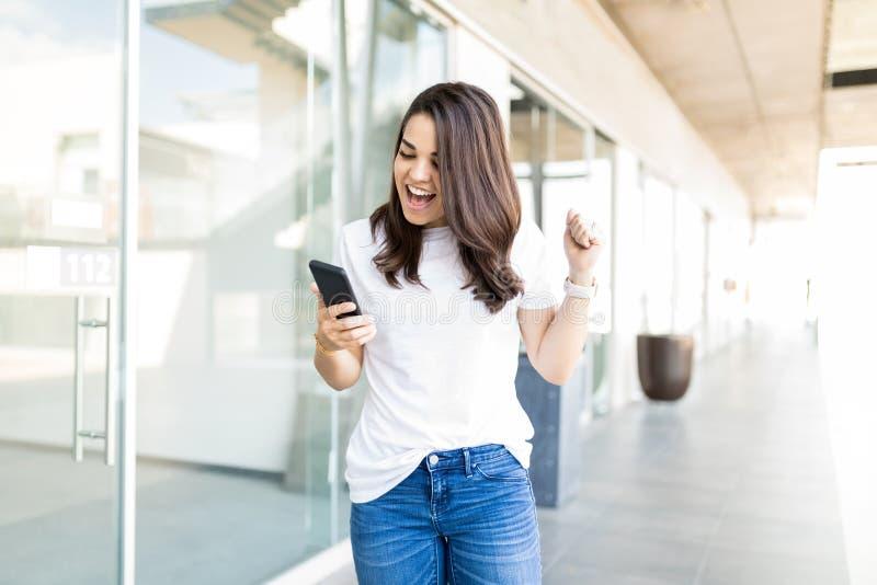 激动的在智能手机的妇女读的惊人的新闻 库存照片