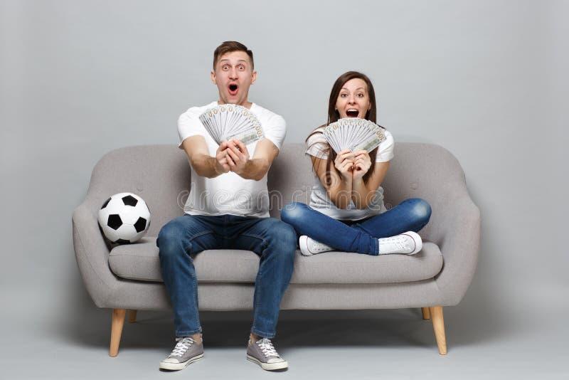 激动的夫妇妇女人足球迷在美元钞票使支持喜爱的队振作,拿着金钱爱好者,现金 库存照片