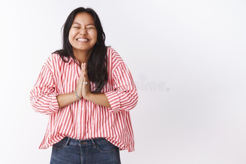激动的女孩不可能等待愿望实现的微笑快乐与握手在的闭合的眼睛祈祷,棕榈一起按了 免版税库存照片