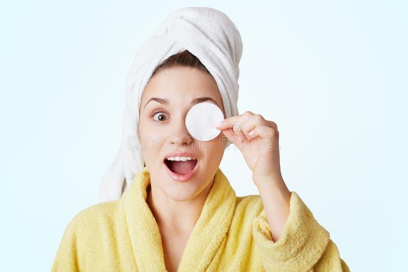 激动的女性画象有毛巾的在头,盖子注视与棉花轮子,展示她的关于秀丽的关心,为日期做准备 免版税库存照片