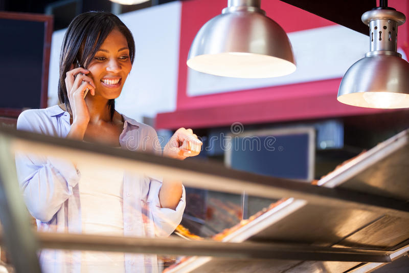 激动的妇女谈话在手机 库存图片