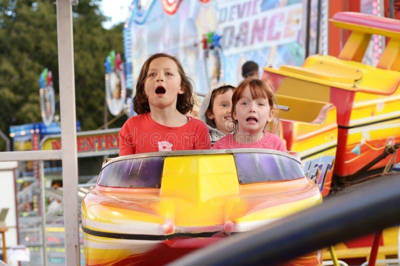 激动的孩子尖叫在狂欢节过山车乘坐 免版税库存照片