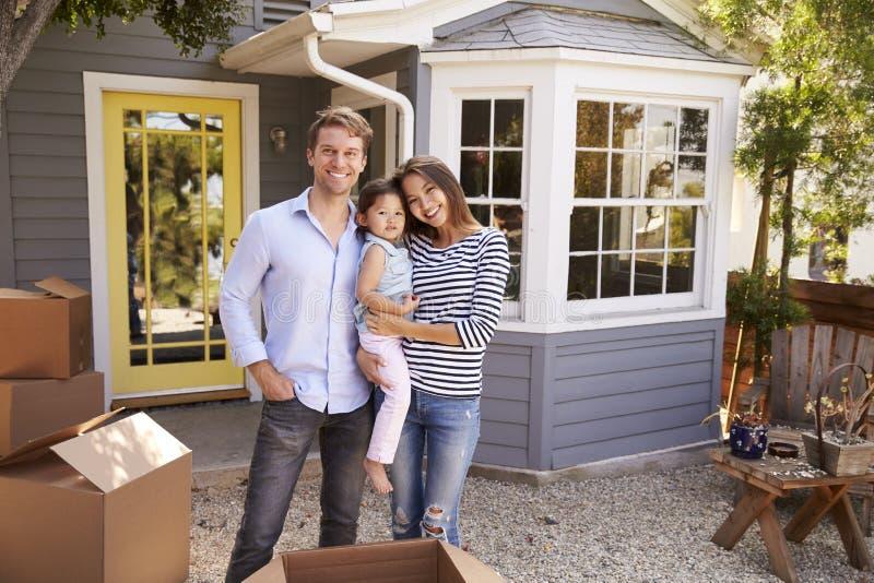 激动的家庭常设外部新的家画象  免版税库存图片