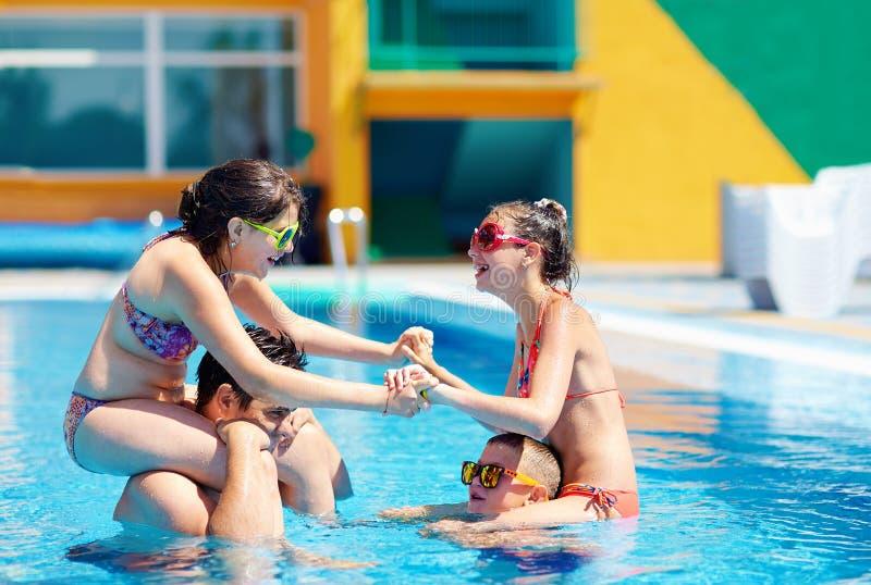 激动的家庭获得乐趣在水池,水战斗 免版税库存照片