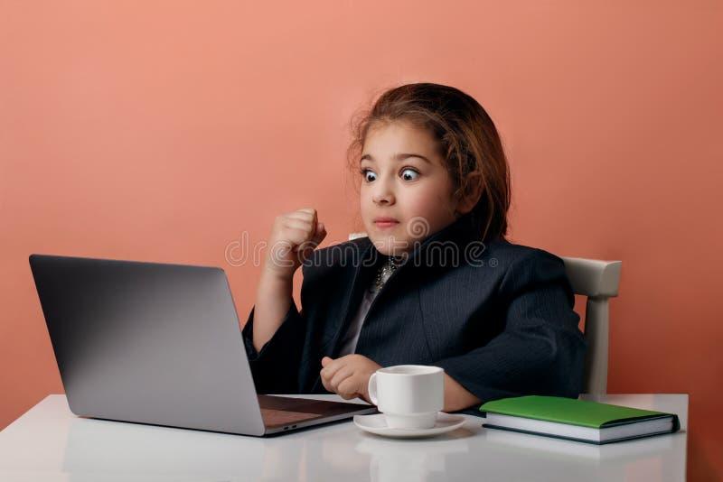激动的年轻佩带的举行的计算机和庆祝成功的画象 免版税库存照片