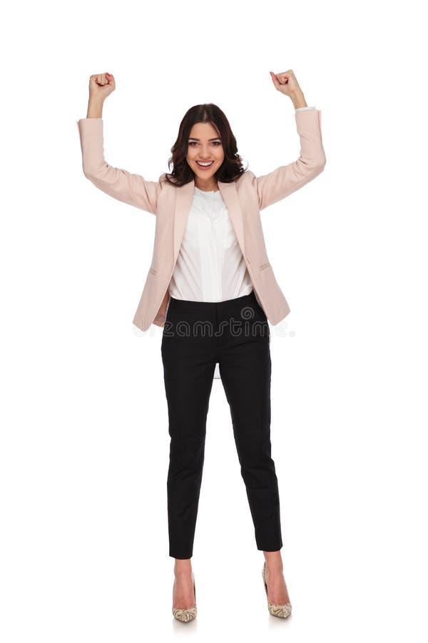 激动的年轻女商人用手上升和被关闭的拳头 免版税库存图片